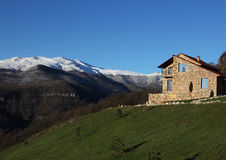 Μόνο σπίτι πετρών στο λόφο στο υπόβαθρο των χιονωδών βουνών, σαφής μπλε ουρανός, οριζόντιος στοκ εικόνες με δικαίωμα ελεύθερης χρήσης