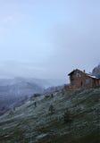 Μόνο σπίτι πετρών στο λόφο στο υπόβαθρο των χιονωδών βουνών, συννεφιασμένος, σκοτεινό στοκ εικόνα