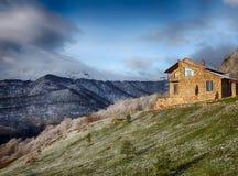 Μόνο σπίτι πετρών στο λόφο στο υπόβαθρο των χιονωδών βουνών, hdr στοκ φωτογραφία