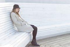 Μόνο λυπημένο όμορφο κορίτσι σε ένα μαύρα παλτό και ένα καπέλο, που κάθονται άσπρο κρύο χειμερινό ηλιόλουστο ημερησίως πάγκων Στοκ φωτογραφία με δικαίωμα ελεύθερης χρήσης