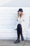 Μόνο λυπημένο όμορφο κορίτσι σε ένα μαύρα παλτό και ένα καπέλο, που κάθονται άσπρο κρύο χειμερινό ηλιόλουστο ημερησίως πάγκων Στοκ φωτογραφίες με δικαίωμα ελεύθερης χρήσης