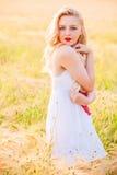 Μόνο όμορφο νέο ξανθό κορίτσι στο άσπρο φόρεμα με το καπέλο αχύρου Στοκ φωτογραφία με δικαίωμα ελεύθερης χρήσης