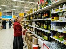 Μόσχα, Ρωσία - 14 Απριλίου 2018 ο αγοραστής επιλέγει το ελαιόλαδο στο κατάστημα Auchan Στοκ Φωτογραφίες