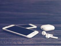 Μόσχα, Ρωσία - 19 Δεκεμβρίου 2017: Άσπρο iPhone, ασύρματα ακουστικά AirPods και ανοικτό κιβώτιο για την επαναφόρτιση των ακουστικ Στοκ Εικόνα
