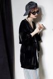 Μόδα που πυροβολείται ενός όμορφου νέου κοριτσιού με μια αναιδή κοντή τρίχα σε ένα ύφος hipster σε ένα μαύρο σακάκι βελούδου σε K Στοκ Φωτογραφίες