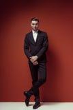 Μόδα που πυροβολείται του κομψού νέου όμορφου ατόμου στο κλασικό μαύρο κοστούμι, Στοκ Εικόνες