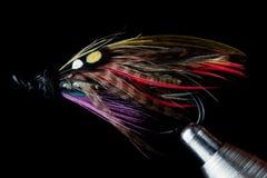 Μύγα αλιείας σολομών στη δένοντας μέγγενη μυγών στο μαύρο υπόβαθρο Στοκ Εικόνες