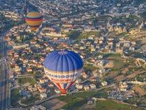 Μύγα δύο μπαλονιών πέρα από το χωριό Goreme στοκ εικόνες