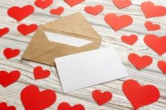 Μύγα καρδιών έξω από το φάκελο αγάπη επιστολών καρδιών φακέλων Ημέρα βαλεντίνων υποβάθρου στο ξύλινο υπόβαθρο Στοκ Φωτογραφίες