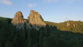 Μύγα μπαλονιών ζεστού αέρα μέσω του ουρανού σε ένα τοπίο των βουνών κοντά στους βράχους απόθεμα βίντεο