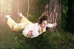 Μύγα σε ένα όνειρο στο φως Νέα γυναίκα στις πυτζάμες στο θερινό πράσινο δάσος Στοκ φωτογραφία με δικαίωμα ελεύθερης χρήσης