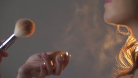 Μύγα ψεκασμών σκονών μακρυά από μια χνουδωτή βούρτσα makeup φιλμ μικρού μήκους