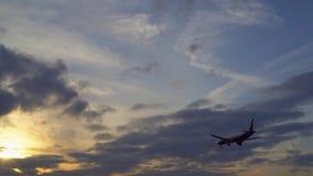 Μύγες αεροπλάνων προς το ηλιοβασίλεμα Οι ακτίνες του ήλιου κάνουν τον τρόπο τους μέσω των πορφυρών σύννεφων απόθεμα βίντεο