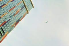 Μύγες αεροπλάνων στο υπόβαθρο ενός ουρανοξύστη με τα ζωηρόχρωμα παράθυρα Στοκ εικόνα με δικαίωμα ελεύθερης χρήσης