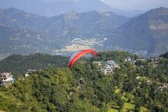Μύγες ανεμόπτερων σε ένα κόκκινο αλεξίπτωτο στα πλαίσια μιας κοιλάδας και των σπιτιών βουνών στοκ εικόνα με δικαίωμα ελεύθερης χρήσης