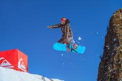 Μύγες ατόμων snowboarder από ένα άλμα στο υπόβαθρο μπλε ουρανού στοκ εικόνες