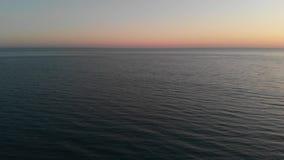 Μύγες καμερών πέρα από τα ωκεάνια κύματα θαμπάδων στον καθαρό ορίζοντα Η κάμερα πετά προς τα εμπρός πέρα από τη θάλασσα στο ηλιοβ απόθεμα βίντεο
