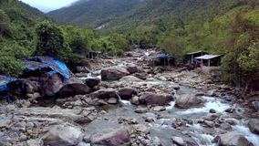 Μύγες κηφήνων κοντά στο δύσκολο ποταμό με τους λίθους και τα φτωχά σπίτια φιλμ μικρού μήκους