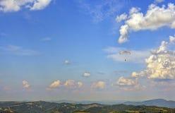 Μύγες Skydiver στον ορίζοντα μέσω των σύννεφων στοκ εικόνες