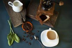 Μύλος καφέ, άσπρο φλιτζάνι του καφέ, φασόλια καφέ και κανάτα γάλακτος Στοκ Εικόνες