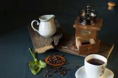 Μύλος καφέ, άσπρο φλιτζάνι του καφέ, φασόλια καφέ και κανάτα γάλακτος Στοκ Φωτογραφίες