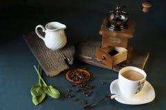 Μύλος καφέ, άσπρο φλιτζάνι του καφέ, φασόλια καφέ και κανάτα γάλακτος Στοκ εικόνες με δικαίωμα ελεύθερης χρήσης