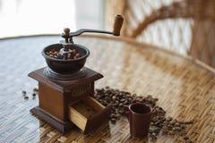 Μύλος καφέ με τα ψημένα φασόλια καφέ στον πίνακα στοκ εικόνες