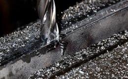 Μύλος τελών του Μπρίτζπορτ CNC που τελειώνει έναν σωρό του πιάτου χάλυβα με τα τσιπ και τον καπνό αρχειοθετήσεων μετάλλων στοκ φωτογραφίες