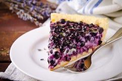 Μύρτιλλο, βακκίνιο ξινό με lavender στο άσπρο πιάτο, ξύλινο υπόβαθρο Στοκ Φωτογραφίες