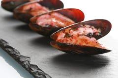 Μύδια στο κοχύλι τους σε ένα μαύρο πιάτο πλακών στοκ εικόνες