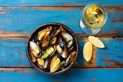 Μύδια στο κύπελλο αργίλου, το ποτήρι του άσπρου κρασιού και το λεμόνι Στοκ φωτογραφία με δικαίωμα ελεύθερης χρήσης