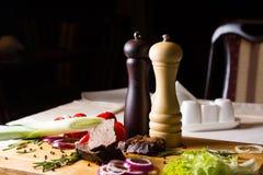 Μύλοι αλατιού και πιπεριών με τα συστατικά στον πίνακα στοκ φωτογραφία