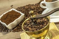 Μύλος καφέ με τα φασόλια καφέ, το φλιτζάνι του καφέ και τον επίγειο καφέ Στοκ εικόνες με δικαίωμα ελεύθερης χρήσης