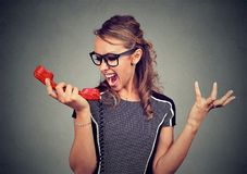 Νέαη γυναίκα που φωνάζει στο κόκκινο τηλέφωνο Στοκ φωτογραφία με δικαίωμα ελεύθερης χρήσης