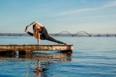 Νέα άσκηση γιόγκας άσκησης γυναικών στην ήρεμη ξύλινη αποβάθρα με το υπόβαθρο πόλεων Αθλητισμός και αναψυχή στη βιασύνη πόλεων στοκ εικόνα με δικαίωμα ελεύθερης χρήσης