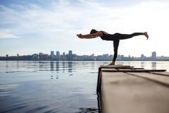 Νέα άσκηση γιόγκας άσκησης γυναικών στην ήρεμη ξύλινη αποβάθρα με το υπόβαθρο πόλεων Αθλητισμός και αναψυχή στη βιασύνη πόλεων στοκ φωτογραφία