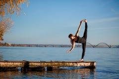 Νέα άσκηση γιόγκας άσκησης γυναικών στην ήρεμη ξύλινη αποβάθρα με το υπόβαθρο πόλεων Αθλητισμός και αναψυχή στη βιασύνη πόλεων στοκ εικόνες