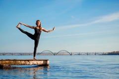 Νέα άσκηση γιόγκας άσκησης γυναικών στην ήρεμη ξύλινη αποβάθρα με το υπόβαθρο πόλεων Αθλητισμός και αναψυχή στη βιασύνη πόλεων στοκ φωτογραφίες