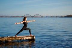 Νέα άσκηση γιόγκας άσκησης γυναικών στην ήρεμη ξύλινη αποβάθρα με το υπόβαθρο πόλεων Αθλητισμός και αναψυχή στη βιασύνη πόλεων στοκ φωτογραφίες με δικαίωμα ελεύθερης χρήσης