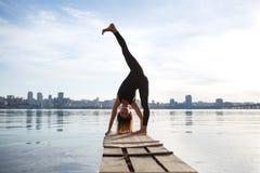 Νέα άσκηση γιόγκας άσκησης γυναικών στην ήρεμη ξύλινη αποβάθρα με το υπόβαθρο πόλεων Αθλητισμός και αναψυχή στη βιασύνη πόλεων στοκ εικόνα