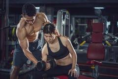 Νέα άσκηση γυναικών σε μια γυμναστική με τη βοήθεια του προσωπικού εκπαιδευτή της, εκπαιδευτικός ικανότητας που ασκεί με τον πελά στοκ εικόνα με δικαίωμα ελεύθερης χρήσης