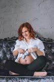 Νέα έγκυος γυναίκα με την κόκκινη συνεδρίαση τρίχας σε έναν γκρίζο καναπέ στο μπαρόκ ύφος Αυτή ` s που φορά ένα άσπρο πουκάμισο,  Στοκ Εικόνες
