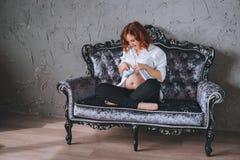 Νέα έγκυος γυναίκα με την κόκκινη συνεδρίαση τρίχας σε έναν γκρίζο καναπέ στο μπαρόκ ύφος Αυτή ` s που φορά ένα άσπρο πουκάμισο,  Στοκ Εικόνα