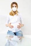 Νέα έγκυος γυναίκα με την προστατευτική μάσκα Στοκ Εικόνα