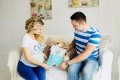 Νέα έγκυος γυναίκα με το σύζυγο στον άσπρο καναπέ στο δωμάτιο που εξετάζει τα ενδύματα μωρών Στοκ Φωτογραφίες