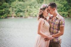 Νέα έγκυος γυναίκα με το σύζυγό της που στέκεται κοντά στη λίμνη Στοκ Φωτογραφία