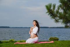 Νέα έγκυος γυναίκα που κάνει τη γιόγκα υπαίθρια Στοκ Εικόνες