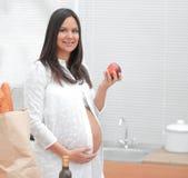 Νέα έγκυος γυναίκα που κρατά τη Apple, που στέκεται στην κουζίνα Στοκ Φωτογραφίες