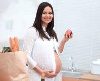 Νέα έγκυος γυναίκα που κρατά τη Apple, που στέκεται στην κουζίνα Στοκ εικόνα με δικαίωμα ελεύθερης χρήσης