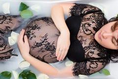 Νέα έγκυος γυναίκα στη χαλάρωση φορεμάτων δαντελλών στο λουτρό με το γάλα Στοκ Εικόνα